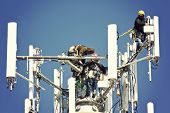 stock photo of work crew  - Crew installing antennas on the top of 150 - JPG