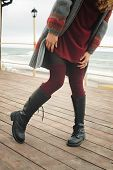 Slim female legs dressed in knee high boots with shoelaces and knitted stockings, outdoor poster
