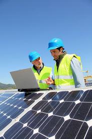 foto of electrical engineering  - Engineers checking solar panel setup - JPG