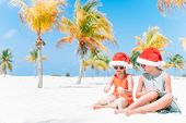 Little Adorable Girls In Santa Hats During Beach Vacation Have Fun Together poster