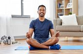 fitness, meditation and healthy lifestyle concept - indian man meditating in lotus pose on exercise  poster