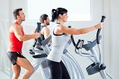 foto of elliptical  - man and woman with elliptical cross trainer in sport fitness gym club - JPG