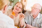 Doctor or Nurse Explaining Prescription Medicine to Senior Adult Couple. poster