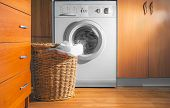 Large Wicker Laundry Basket, Lid Opened, Near The Front Load Washing Machine With Laundry. House Int poster