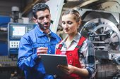 Woman and man manufacturing worker in discussion writing on tablet computer  poster