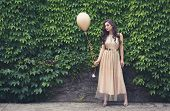 Teen Girl In Glamorous Golden Dress Standing By The Green Wall Holding Balloon. Ready For Her Prom O poster