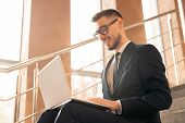 Young successful broker in formalwear talking through video-chat in front of laptop while sitting on poster
