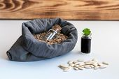 In A Bag Of Natural Flax, Filled With Plant Seeds, There Is A Glass Jar For Storing Seeds. The Conce poster