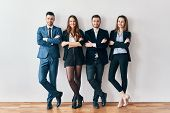 Full Length Portrait Of Young And Smiling Business People With Arms Crossed Lean To Wall In Office.  poster