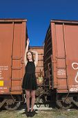 stock photo of boxcar  - Beautiful teenage woman standing next to railway boxcars in a railroad yard - JPG