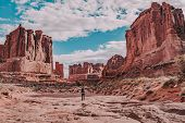A Hiker In The Scenic Landscape Of Park Avenue In Arches National Park, Moab, Utah, Usa. Red Rocks A poster