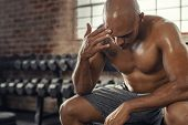Exhausted shirtless man sitting on bench at gym. Sweaty muscular guy resting after fitness training  poster