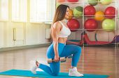 Fitness Woman Exercising Cross Fit Holding Dumbbells. Fitness Instructor In The Sport Room Backgroun poster