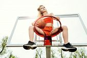 A full length portrait of a sporty teenager girl posing on the basketball pinch. Sport fashion, acti poster