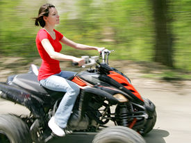 picture of four-wheelers  - young adult female riding a 4 wheeler on a dirt road with good panning motion blur - JPG