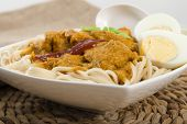 image of ayam  - Dry Curry Mee - Malaysian chicken curry with coconut milk and noodles served with boiled egg on a woven mat.