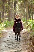 pic of bareback  - woman in medieval dress riding galloping horse through forest - JPG