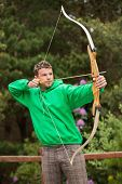 picture of archery  - Focused man practicing archery at the range in the countryside - JPG
