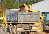 picture of oversize load  - Excavator scoops up a huge bucket and is about to empty it into the rear tray of the haulage truck - JPG