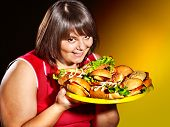 pic of high calorie foods  - Overweight woman holding hamburger - JPG