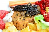 stock photo of morel mushroom  - Macro shot of pork steak with Morel mushrooms French recipe on white plate with French fries red pepper in olive oil with garlic vegetables and strawberries - JPG