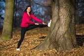 Woman exercising in autumn park