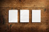 Постер, плакат: Three used memo pads on an old grungy wooden surface For inserting your messages