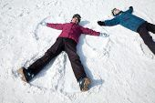 stock photo of down jacket  - Man and Woman Lying on the Snow Making Snow Angel - JPG