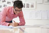stock photo of button down shirt  - Businessman working on architecture project in the office - JPG