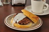 stock photo of biscuits gravy  - Sausage and biscuit with country gravy and a cup of coffee - JPG