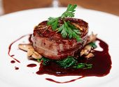 stock photo of bacon  - Tenderloin steak wrapped in bacon with red sauce and spinach - JPG