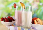 stock photo of fruit shake  - Delicious milk shakes with strawberries and peach on wooden table on natural background - JPG