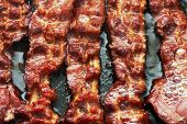 stock photo of bacon  - Bacon slice being cooked in frying pan - JPG