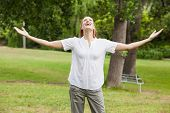 Smiling young woman with arms outstretched at the park