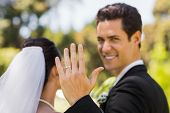 Close-up of a bridegroom showing his wedding ring to the camera in the park