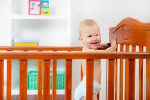 foto of playtime  - Baby boy standing in crib at home - JPG