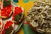 Sandwiches with red caviar and squid salad with mushrooms and green peas on the holiday table