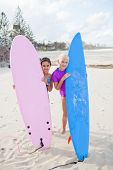 Two Happy Young Girls Holding Surfboards At Beach