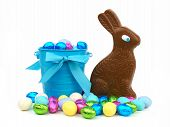 stock photo of easter candy  - Easter candy in a blue pail with a chocolate bunny over a white background - JPG