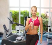 fitness and gym concept - sporty woman with bottle of water at gym