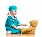 picture of throat  - Adorable child dressed as doctor playing with toy over white - JPG