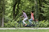 picture of tandem bicycle  - Young couple riding bicycle in the park - JPG