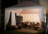 stock photo of banquette  - Garden party or wedding entertainment tent in garden at night - JPG