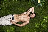 picture of shirtless  - Good looking shirtless fit male model relaxing lying on the grass shot from above - JPG