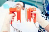 stock photo of icu  - defibrillator electrodes in hands - JPG