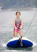 stock photo of ski boat  - Young Girl riding a ski tube behind a boat - JPG