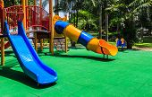 stock photo of playground  - Colorful Playground with Green Elastic Rubber Floor for Children in the Park  - JPG