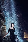 picture of night gown  - Beautiful woman in black dress posing near waterfall - JPG