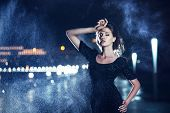 picture of night gown  - Beautiful woman in black dress posing on a city lights background - JPG