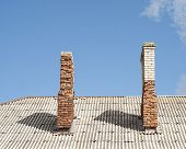 stock photo of chimney  - red and white brick chimney on the roof blue sky background - JPG